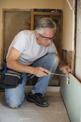 Caucasian man using screwdriver