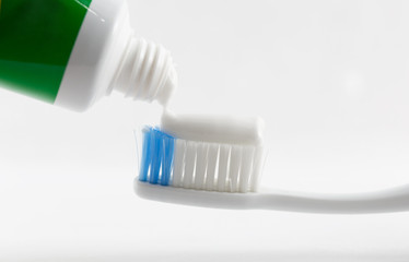 Hand press Toothpaste on tooth brush.
