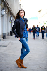 Young beautiful girl in blue jeans and a blue shirt on the backg