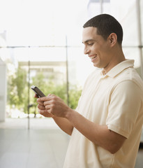 Hispanic man text messaging on cell phone