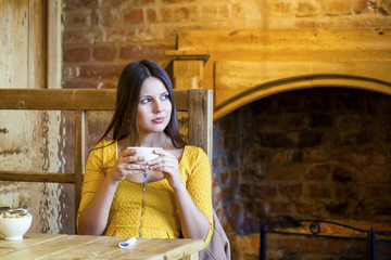 Beautiful brunette girl sitting in a coffee shop
