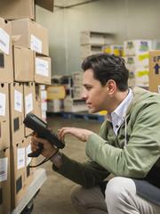 Hispanic worker scanning boxes in walk-in freezer