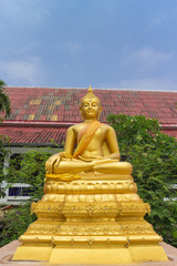the gold buddha statue sitting under sunlight