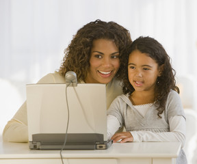 African mother and daughter looking at web cam