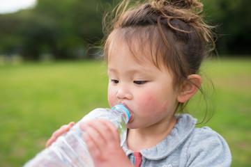 ペットボトルの水を飲む女の子