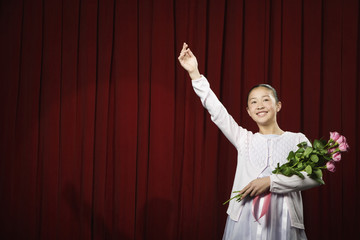 Asian girl waving and holding flowers on stage