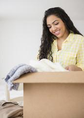 Hispanic woman unpacking cardboard box