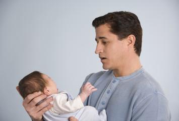 Hispanic father holding baby