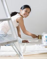 Pacific Islander woman painting baseboard