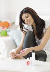 Mixed Race woman painting toenails