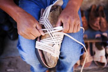 Close up of craftsman weaving sandal in shop