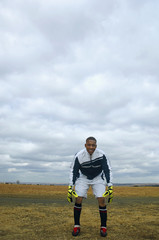 Mixed race man in soccer uniform standing in remote field