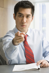 Korean businessman pointing and looking serious