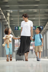 Chinese mother and daughters on train platform