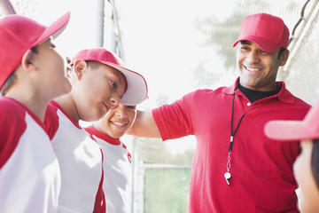 Multi-ethnic boys in baseball uniforms with coach
