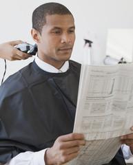 African man reading paper at barbershop