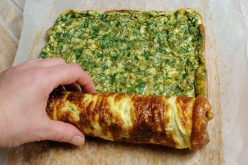 Fastening omelette with herbs in roll