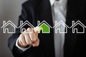 Businessman choosing house, real estate concept.