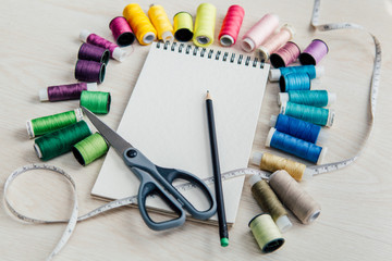 colorful sewing thread spools and a notebook