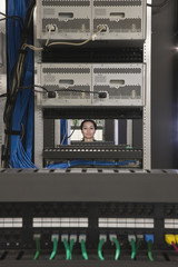 Mixed Race woman looking through computer servers
