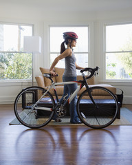 Pacific Islander woman with bicycle in livingroom