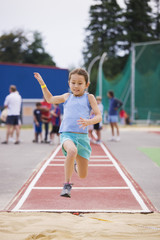 Asian girl performing long jump