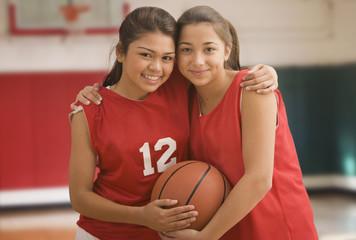 Multi-ethnic girls hugging in basketball uniforms
