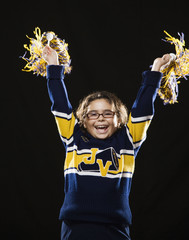 Mixed race girl cheering in cheerleader outfit