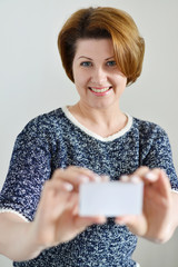 Adult woman holding a white  card in hand
