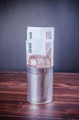 thai banknote on silver can with wooden background