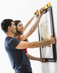 Couple measuring picture frame on wall