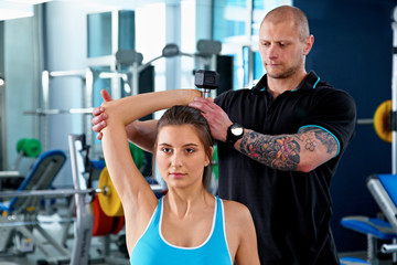 Woman with Personal Trainer in Gym, blured background