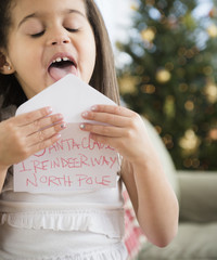 Hispanic girl sealing envelope for Santa