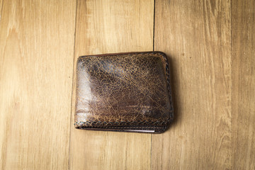 brown leather wallet on wood board background