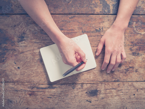 Woman writing in notepad at wooden table - 82186243
