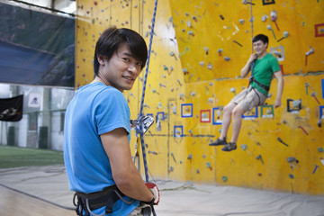 Spotter with Chinese man scaling rock wall