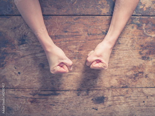 Female fists on a wooden table - 82187457