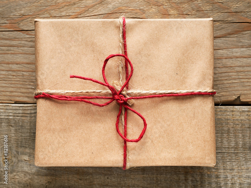 Gift box close-up top view on wooden background - 82187616