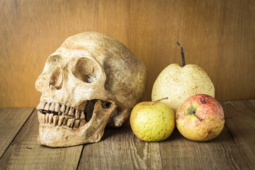 skull and sear fruit still life on wood background