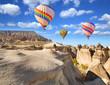 Leinwandbild Motiv Hot air balloon flying over rock landscape at Cappadocia Turkey.