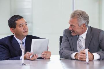 Businessmen using tablet computers in meeting