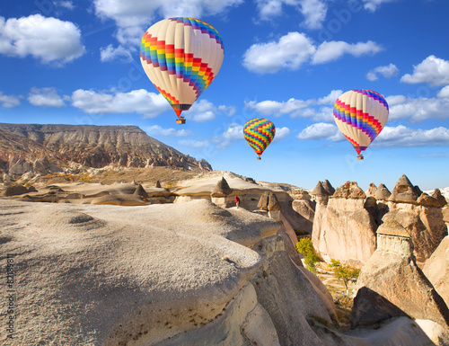 Hot air balloon flying over rock landscape at Cappadocia Turkey.