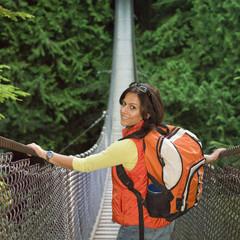 Indian woman wearing backpack on footbridge