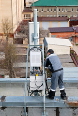 Мастер ремонтирует базовую станцию сотовой связи