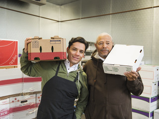 Workers carrying boxes in walk-in freezer