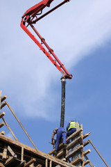 Builder worker with tube from truck mounted concrete pump