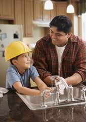 Hispanic father and son wearing hard-hat washing hands in kitchen
