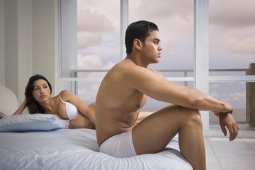 Hispanic couple arguing on bed
