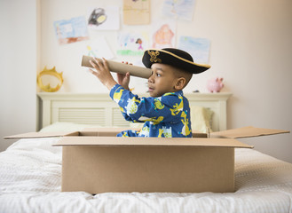 African American boy playing in cardboard box