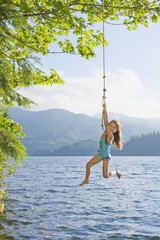 Asian girl hanging from lake rope swing